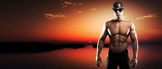 Muscled swimmer man with cap and glasses outdoor at a lake at su