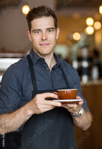 Barista Standing in Cafe with Cup