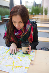 Cute girl with map at open cafe