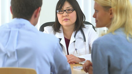 Caucasian couple talking to Japanese doctor