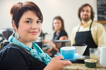 Woman Holding Coffee Cup With Owners in cafe