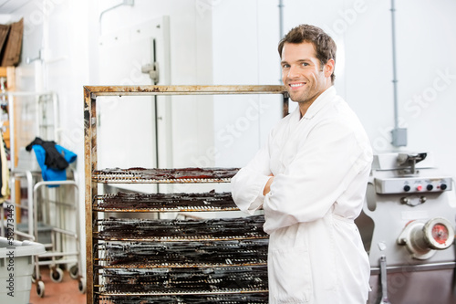 Confident Worker Standing By Rack Of Beef Jerky At Shop