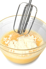 Cooking, whipping eggs with electric whisk in bowl, close up