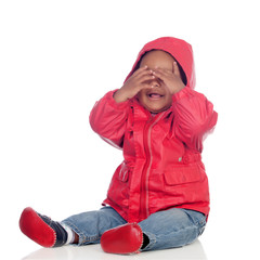 Adorable african baby sitting on the floor with red raincoat cov