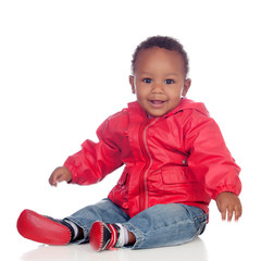 Adorable african baby sitting on the floor with red raincoat