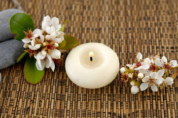 bunch of spring flower, candle, massage oil, stones on mat