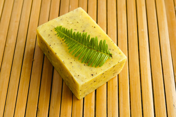 Bar of natural handmade soap with fern on wooden mat