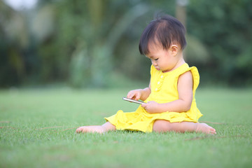 baby girl touch screen her smartphone on lawn