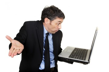 Businessman shrugging as he reads his laptop