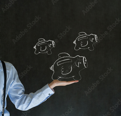 Businessman holding chalk flying piggy banks on blackboard