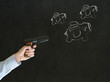 Businessman shooting at chalk flying piggy banks on blackboard