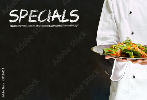 Chef with chalk specials sign on blackboard background