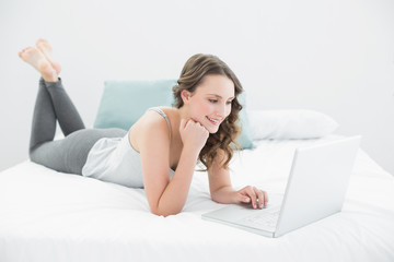 Smiling casual brunette using laptop in bed