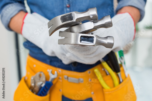 Mid section of handyman holding hammers with toolbelt around wai