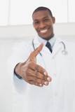 Smiling male doctor offering a handshake