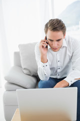 Casual young man using cellphone and laptop on sofa