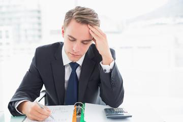 Worried businessman sitting at office desk