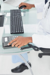 Low section of doctor using computer at medical office