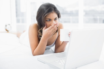 Shocked woman drinking coffee while using laptop in bed
