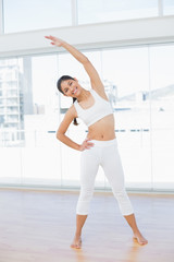 Happy woman stretching hand in fitness studio
