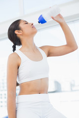 Young woman drinking water in fitness studio