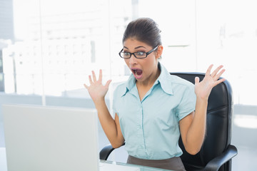 Shocked businesswoman looking at laptop in office