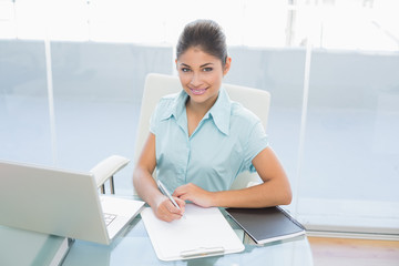 Businesswoman with laptop writing document in office