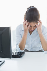 Businesswoman suffering from headache in front of computer