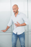 Casual young man with stomach pain at home
