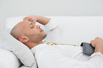 Businessman sleeping on sofa with digital tablet at home