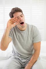 Sleepy man yawning as he rubs his eye in bed
