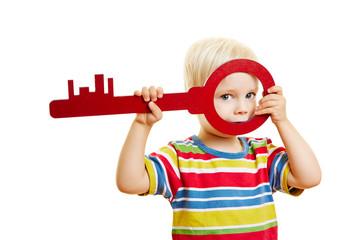 Kind schaut durch einen großen Schlüssel