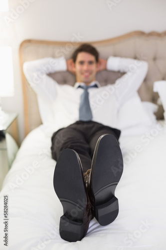 Relaxed smiling well dressed man lying in bed