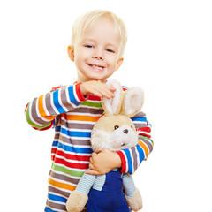 Glückliches Kind streichelt Kuscheltier