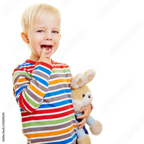 Zahnendes Kind hält Finger an Mund