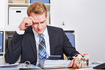 Stressed businessman with burnout in office