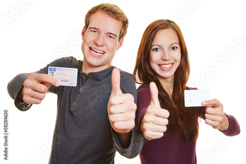 Man and woman with drivers licence holding thumbs up