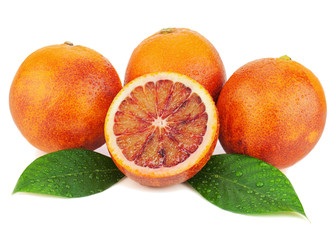 Ripe red blood oranges with cut and green leaves isolated on whi