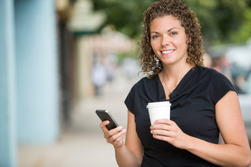 Happy Woman With Coffee Cup Using Smartphone