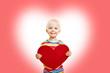 Kind hält rotes Herz zum Muttertag