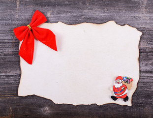 Blank paper againts wooden background with red bow and Santa Cla