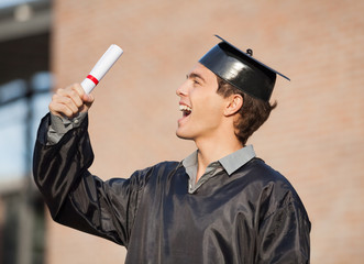 Student Holding Diploma On Graduation Day In College