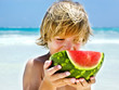 boy eating a slice of watermelon on the beach