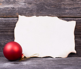 Christmas background with red bauble and blank paper