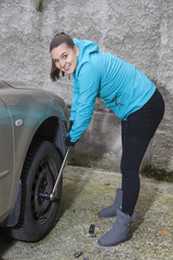 Cute young woman driver loosening nuts on car wheel