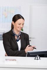 mitarbeiterin an der rezeption schaut auf  computer
