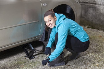 Pretty smiling girl lifting her car before replacing car tyres