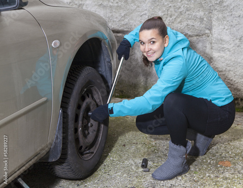 Cute young woman driver loosening nuts on a car wheel