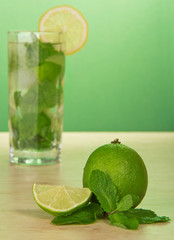 Mojito cocktail, slice of a lemon, and spearmint leaves