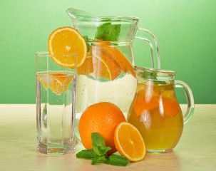 Jugs with drinks, glass, oranges and spearmint